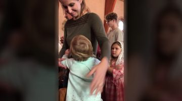 Adorable little girl hugs everyone on their way to receive communion