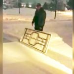 Wife catches husband using giant table as a shovel to clear snow from the driveway